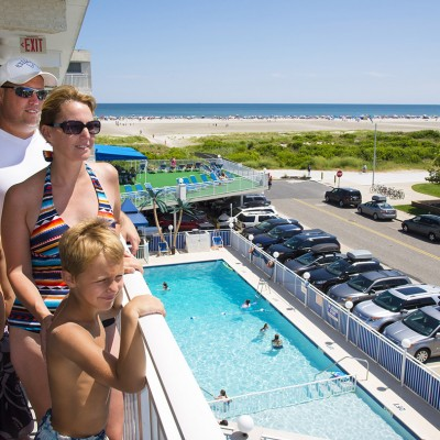 Family on balcony overlooking pool and Wildwood beach at Armada by the Sea